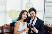 Young couple celebrating new year together, drinking wine together.