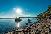A sunstar over some rocks at the seaside of the german island Ruegen