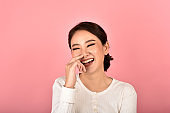 Asian woman laughing and enjoy on pink background, Portrait of happy smiling middle age woman in casual clothes looking at the camera.