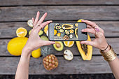 Photographing on smart phone variety of exotic fruits
