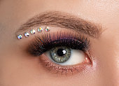 Woman's blue green eye with beautiful make-up and thick eyebrows, crystals under the eyebrow  close up.  Looking at the camera. Professional makeup and cosmetology.