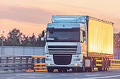 Freight truck moves on the highway at sunset time.