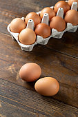 Chicken eggs in an open egg carton on wood background. Top view with copy space.