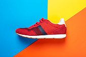 One new fashionable red men's sneakers on a bright background.