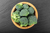 Fresh raw broccoli in a wooden bowl on a wooden table.