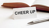 piece of paper with text Cheer Up on the background of books, pens, on a white background