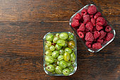 Assorted berries of raspberries, gooseberries in glass bowls on a wooden table.