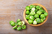 raw brussels sprouts in a plate on a wooden background
