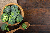 Fresh broccoli with in bowl on wooden table close up.