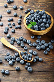 Freshly picked blueberries in wooden bowl on a wooden  table. Healthy fruits.