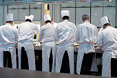 Group of chefs in white uniform busy to preparing food for they client