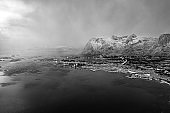 Outstanding winter photo of Lofoten Islands fishing village. Overcast sky above snowy mountain peaks and fjord.