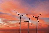 Wind turbines as alternative renewable energy on a background sunset sky.