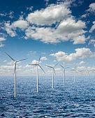 Row from wind turbines in an open sea water on a background of cloudy sky.