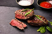 Juicy medium rare beef steak on board with herbs spices and salt.