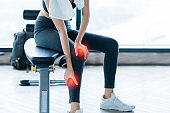 sport accident concept body hurt in gym asian female hand touch body part with pain from wrong action workout in fitness gym