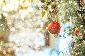 Beautiful red and gold Christmas Bauble hanging on decorated Christmas tree festive christmas eve background concept