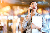 Asian female business owner hand communication with smartphone and laptop business technology with blur deaprtment store bokeh background