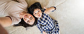 happy Asian Family mother and daughter making a fun face selfie photo while lay down on floor use in living room home background.
