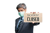 Businessmen wear medical masks on the isolated background and holding sorry we are closed sign. Concept of businesses and shops have to close because of a virus epidemic and quarantine
