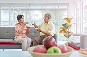Asian Elderly retired couple cheer and drink hot tea while relaxing at home for healthy lifestyle concept.