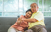 Elder Couple is excited while watching horror scary movie on TV at home the couch