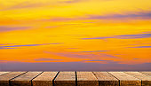Empty display wooden board shelf table counter with copy space for advertising backdrop and background with orange sunset sky.