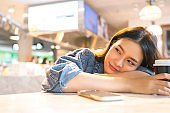 young asian traveller female sit relax facial expression hand use smartphone waiting for aboard time in cafe restaurant at airport departure terminal