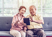 Senior couple is waving to family on Video Call communication technology on tablet on a sofa at home