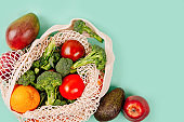 Top view of mesh shopping bag with organic eco vegetables on pink background.
