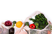 Top view of mesh shopping bag with organic eco vegetables isolated on white