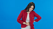 Female suffering from digestive problems. Bearded woman wearing white t-shirt sudden stomach ache, severe abdominal pain, constipation, gastritis, pancreatic diseases. Blue background.