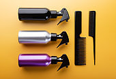 Hairdresser equipment: spray bottles and hair combs isolated on yellow background