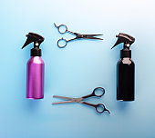 Spray bottles and scissors for haircut isolated on blue background, top view