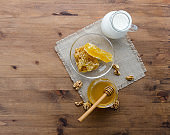Honey, milk and walnut on retro wooden background, top angle view