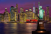Statue of Liberty and New York City Skyline with Manhattan Financial District and World Trade Center at Sunset.