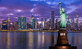Statue of Liberty and New York City Skyline with UN Building, Chrysler Building and Empire State Building at Sunset.