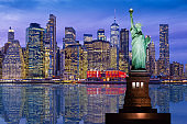 Statue of Liberty and New York City Skyline with Manhattan Financial District and World Trade Center, Reflected in East River at Sunset.