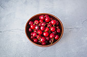 Sour cherries for snack in summer season.Tasty natural dessert food served in ceramic brown bowl on table at home