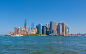 New York City Skyline with Manhattan Financial District, World Trade Center, Water of New York Harbor, Battery Park and Blue Sky.