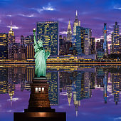 Statue of Liberty and New York City Skyline with UN Building, Chrysler Building and Empire State Building, Reflected in East River at Sunset.