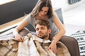 Dark-haired young woman covering her husband with a plaid