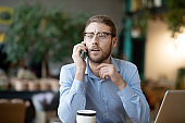 Young businessman in glasses talking positively on a smartphone.