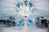 Happy bride in a white wedding dress in a beautifully decorated banquet room outdoors