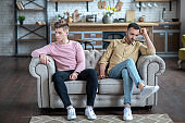 Two men sitting on the sofa not loooking at each other looking upset