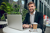 Handsome young businessman working outside and smiling