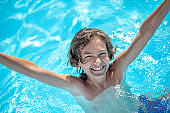 Smiling boy in water on shoulders with hands up