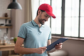 Delivery person in a red hat looking at the waybill and smiling