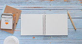 Top view white binder blank notebook or diary or journal for writing text and message with pencil and coffee cup on blue pastel wood background with copy space. Still lifestyle photo concept.