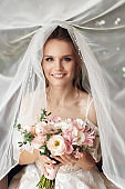 Young beautiful bride in white elegant dress getting ready for the wedding ceremony
